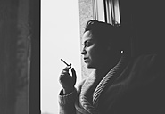 Spain, Galicia, Naron, Adult woman smoking in the window of her home - RAEF000043