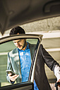 Young businessman with cell phone getting into car - UUF003412