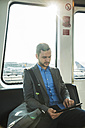 Germany, Frankfurt, young businessman in bus at the airport - UUF003420