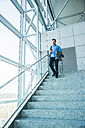 Young businessman walking on stairs looking on cell phone - UUF003424