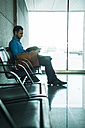 Young businessman with digital tablet at waiting area - UUF003426