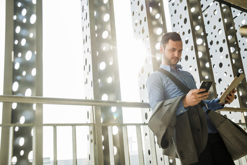 Young businessman holding cell phone and digital tablet - UU003437