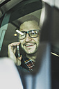 Smiling young businessman talking on cell phone in car - UUF003438