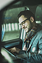 Young businessman in car looking at digital tablet - UUF003440