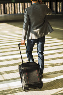 Young businessman with baggage walking in car park - UU003445