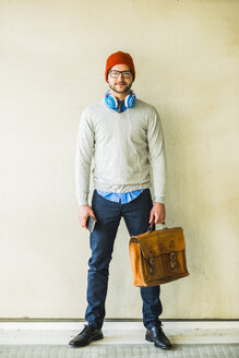 Portrait of stylish young man with leather bag - UUF003453