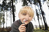Little boy looking through magnifying glass at viewer - PDF000817