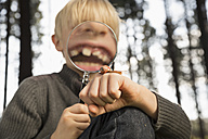 Little boy watching snail with magnifying glass in a forest - PDF000823