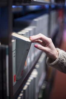 Close-up of woman in library taking book from shelf - CHPF000063