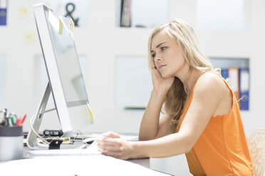 Creative office woman sitting behind her computer - ZEF002979