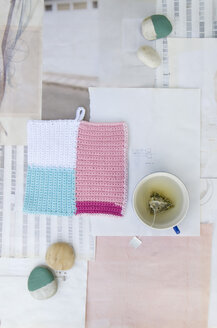 Crocheted potholder, pebbles and cup of tea on sketches - GIS000026