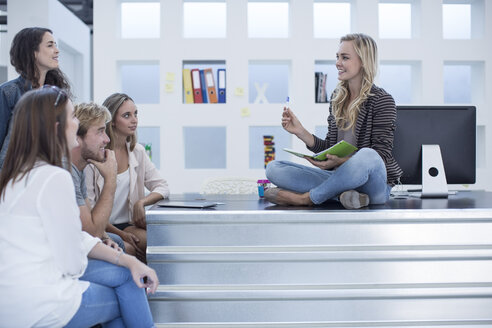 Creative office woman sitting on her desk and meeting with her colleagues - ZEF003020