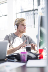 Creative office man working on his computer and wearing a headset - ZEF003088