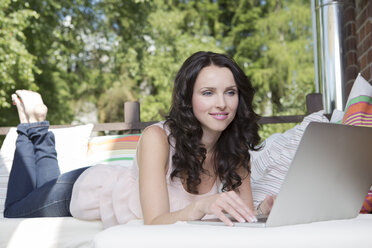 Portrait of woman using laptop on her balcony - VTF000398