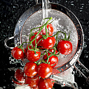 Cherry tomatoes in a colander being washed on a mirror face - CSTF000867