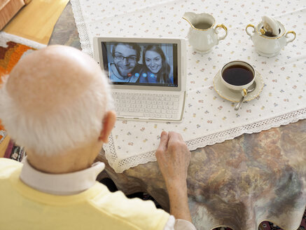 Grandfather videoconferencing with grandchildren via digital tablet - LAF001326