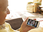 Grandfather videoconferencing with grandchildren via smartphone - LAF001333