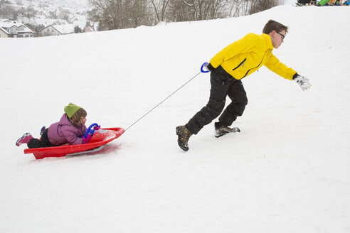 Germany, Swabian mountains, brother pulling his little sister lying on sledge - LVF002913