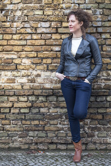 Portrait of woman with curly brown hair leaning at brick wall - ANHF000001