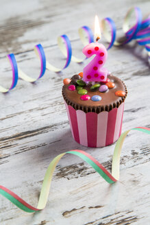 Birthday muffin with chocolate buttons and lighted candle - SARF001408