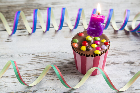 Birthday muffin with chocolate buttons and lighted candle - SARF001413