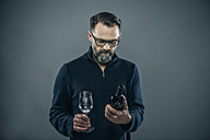 Man with red wine glass and wine bottle - IPF000190