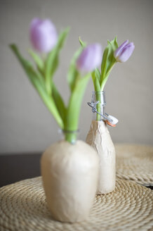 Glass bottles wrappes with packing paper used as flower vases - GIS000019