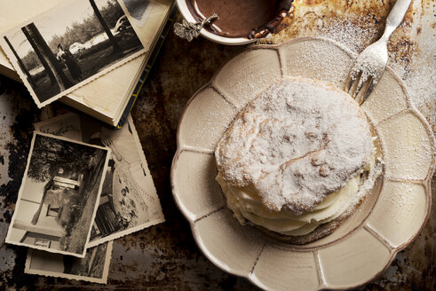 Sliced bun filled with whipped cream, cup of hot chocolate and old photographies - CSTF000882