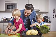 Father preparing food in kitchen with children - RHF000573