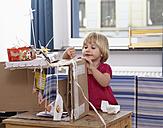 Little girl tinkering with cardboard box - RHF000585