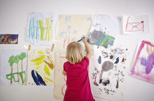 Little girl painting on wall of children's room, rear view - RHF000595