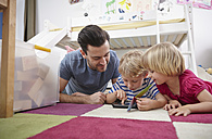 Father and children using mini tablet, lying on floor - RHF000601
