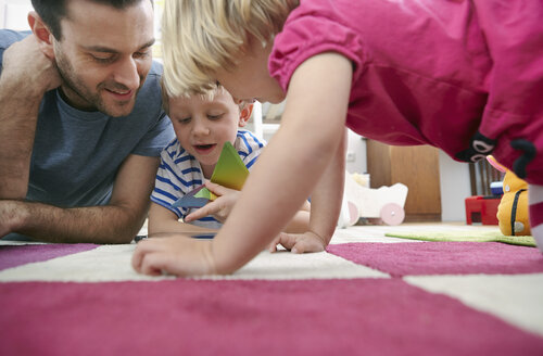 Father and children using mini tablet, lying on floor - RHF000604