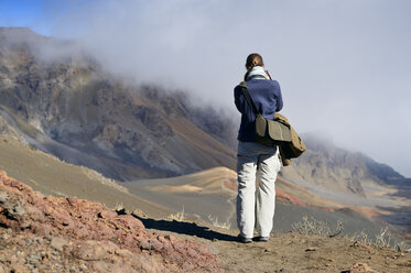 USA, Hawaii, Maui, Haleakala, woman taking picture of volcanic landscape with cinder cone - BRF001077