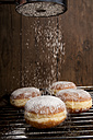 Sprinkling Bismarck doughnuts with icing sugar - CSTF000881