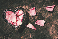 Heart-shaped glass and rose petals on dark wood - DEGF000352