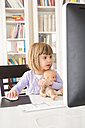 Portrait of little girl with doll spending time at computer - LVF002925