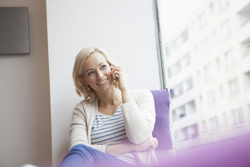 Portrait of smiling woman telephoning with smartphone at window - RBF002452