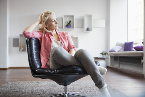 Woman relaxing on leather chair at home - RBF002487