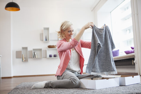 Woman with purchase at living room - RBF002502