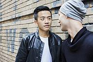 China, Hong Kong, gay couple at house wall - JUBF000002