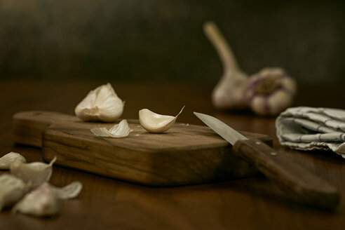 Garlic cloves and knife on wooden board - DIKF000133