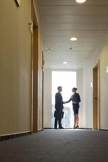Businesspeople in corridor shaking hands - WESTF020851