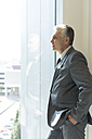 Businessman looking out of window - WESTF020866