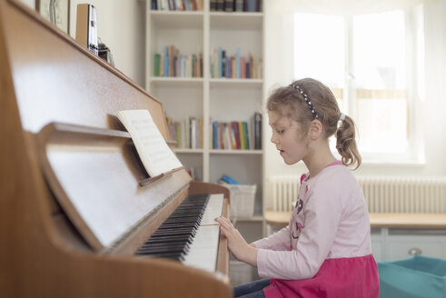 Little girl playing piano at home - OPF000048