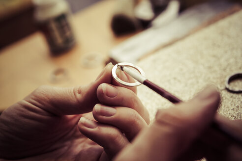 Goldsmith working on wedding rings, applying chemical on surface - KRPF001305