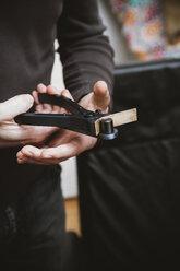 Goldsmith working with pliers on wedding ring work piece - KRPF001307