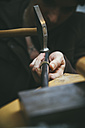 Goldsmith working with hammer on wedding rings - KRPF001314