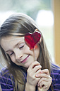Girl holding heart-shaped lollipop - SARF001430