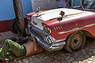Cuba, Trinidad, man repairing his vintage car - EJW000686